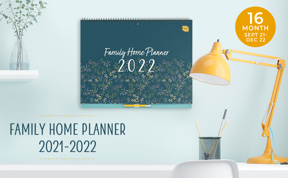 Family Home Planner on an office wall above a desk with lamp and pen pot, next to an office chair