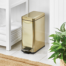 soft brass rectangular step trash can in a bathroom setting, white stand, towels, plant, white walls