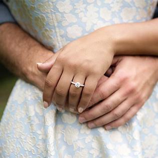Man embracing woman  wearing engagement ring