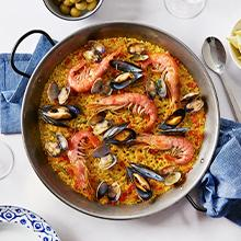 A bowl of homemade Spanish seafood paella and seasoned with pure saffron on a marble table