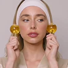 Image showing female using ice globes to soothe and massage the cheeks.