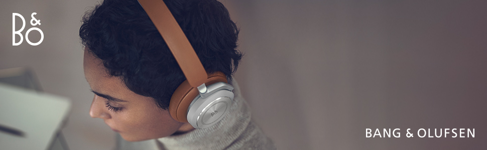 A woman wearing over-ear headphones Beoplay HX in Timber colour