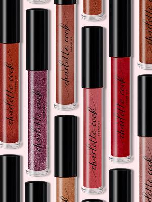 Assorted Charlotte Cook Cosmetics Lip Gloss Bottles on Pink Background