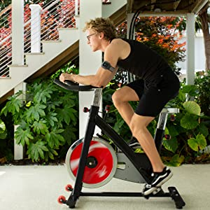 a man is riding a stationary bike with actionsleeve on his arm to track his progress