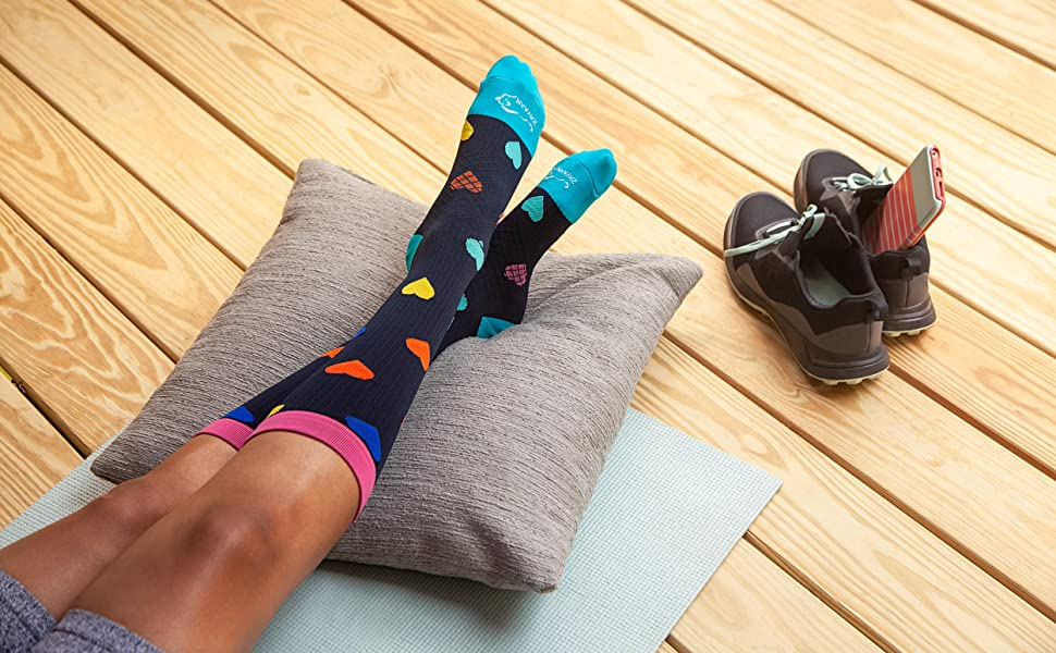 Woman wearing compression socks on a deck relaxing after a workout..