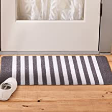 A white and black stripped entrance mat keeps dirt from entering the house with style