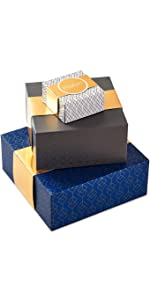 Assorted gift boxes with wrap bands in black, blue and white with gold accents