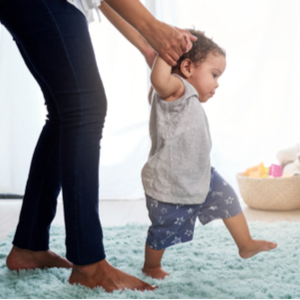 Woman helping a baby walk on a plush indoor area rug