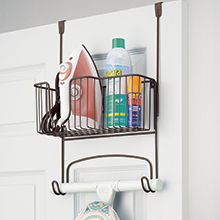 bronze over the door rack with basket holding iron and bottles attached to back of a white door