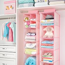 hanging pink fabric closet organizer with baby clothes, white closet setting, dresser, box, shirts