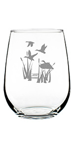 Design of ducks flying over a pond with reeds, hand engraved on a stemless wine glass.