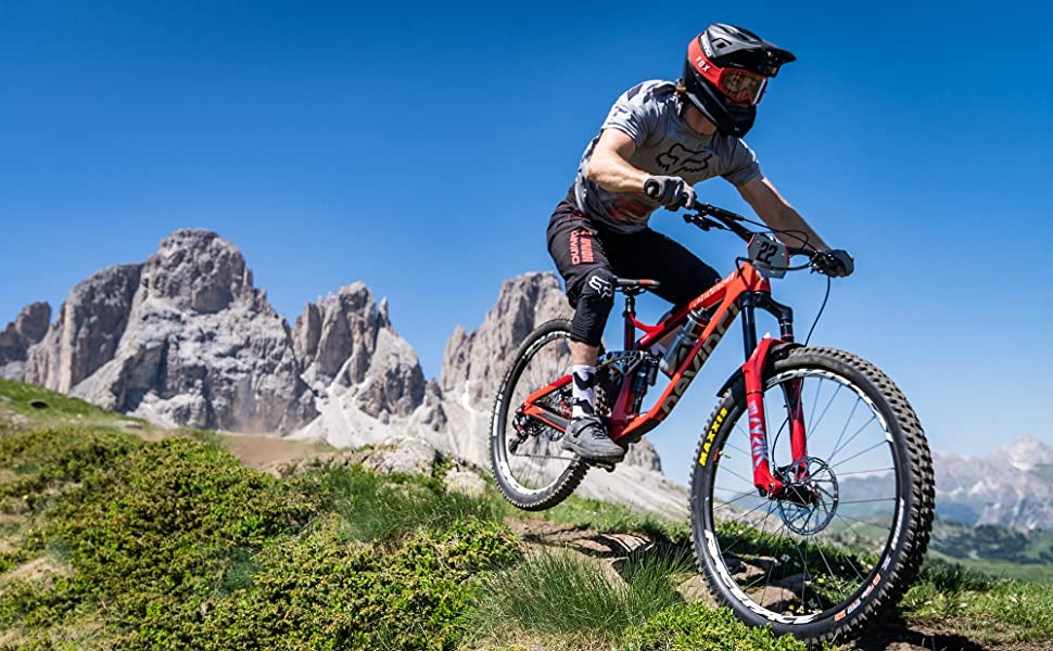 Enduro bike rider going down hill with mountains in background.