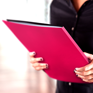 womanamp;#39;s hands holding berry red presentation binder