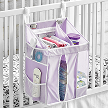 closeup of white crib with purple hanging diaper caddy holding diapers, cream, baby brush, wipes