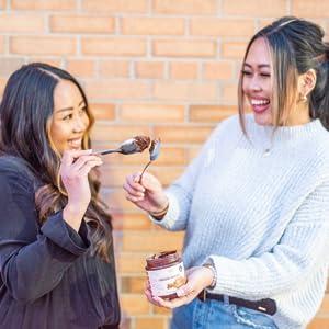 Two women touching spoons coated in ChocZero Hazelnut Spread