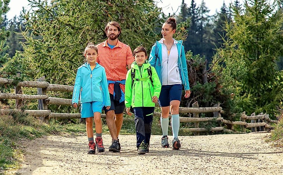 Famiglia che cammina in un sentiero con abbigliamento outdoor sportivo CMP