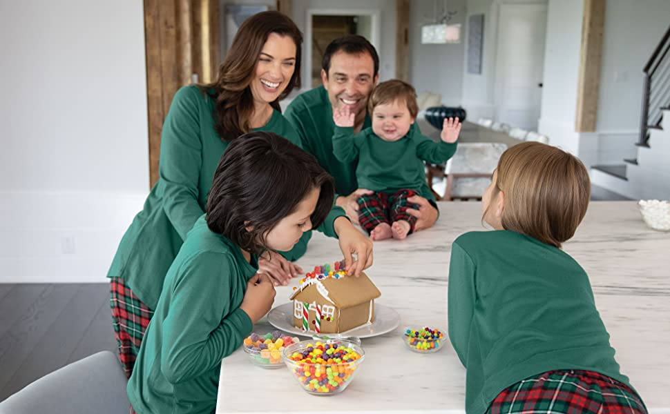 Family gathered around kitchen table in matching holiday pajamas