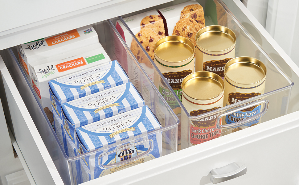 Two clear plastic storage bins inside a white open kitchen drawer with dry food and pantry snacks
