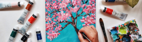 Image of a painting of cherry blossoms with paint supplies on the side
