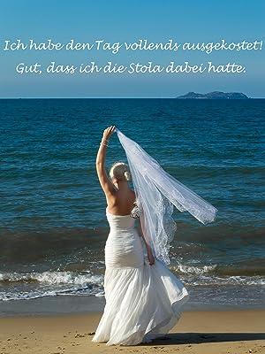 Braut am Strand hält wehenden Schleier hoch