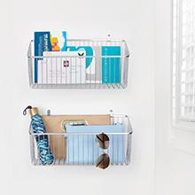 white metal basket mounted on white wall holding umbrella, books, mail, sunglasses