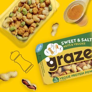 Een plastic bakje vol met de noten mix van graze en twee lepels met honing