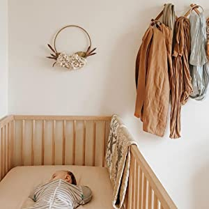 baby lying in a crib with a muslin crib sheet