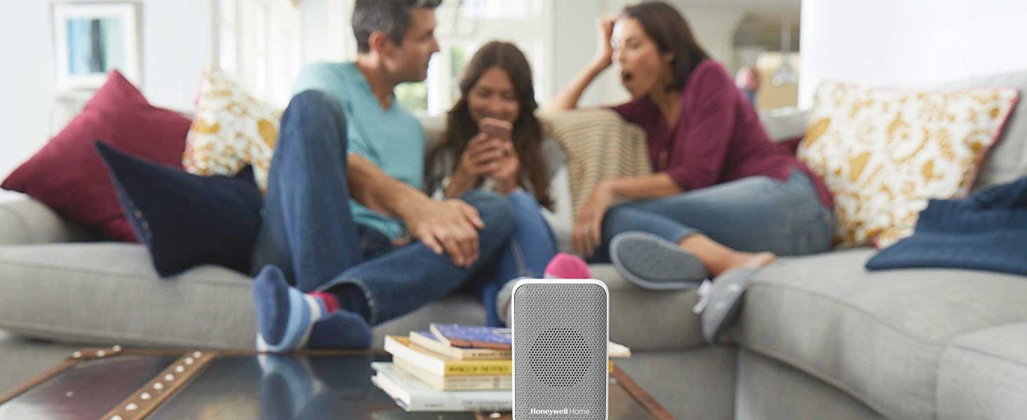 Family in living room on couch together, wireless doorbell in foreground