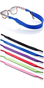 glasses straps laid on white table with one strap attached on a pair of glasses