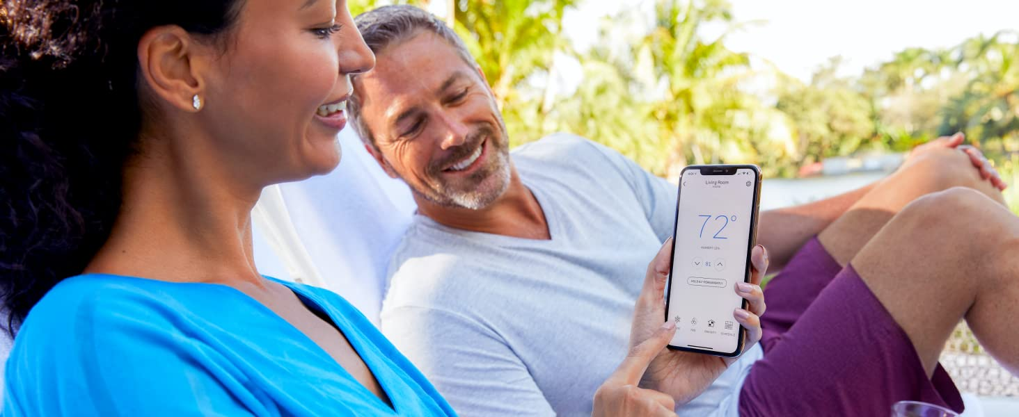 Woman using the Honeywell Home app while relaxing outside