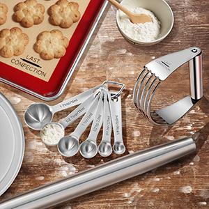 measuring spoons, rolling pin, dough blender, cake pan, cookie sheet, baking mat, cookies, flour