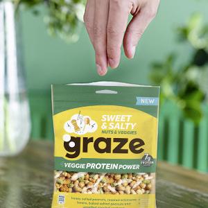 Een hand met de zak van de noten mix van graze, met cashews, pindas edamame bonen