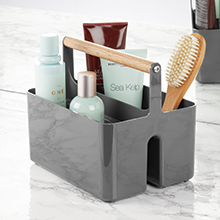 grey shower caddy, wood handle, holding brush, bath bottles, tubes on gray counter, mirror in back