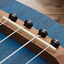 dark blue ukulele front, walnut bridge with pins, four Aquila strings, GraphTech NuBone saddle