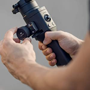 Hands holding the DJI Stabilizer while turning the focus dial