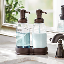 two clear soap pumps with bronze tops and base on a bathroom marble sink top, faucet, mirror, plant