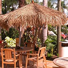 A commercial umbrella covered with a Mexican Straw Grass Thatch Cape for a tropical feel