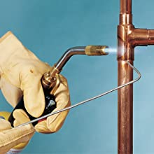 Blow torch soldering copper water piping together.