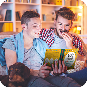 """Image of couple sitting on a couch enjoying """"100 Things I Love About You""""."""
