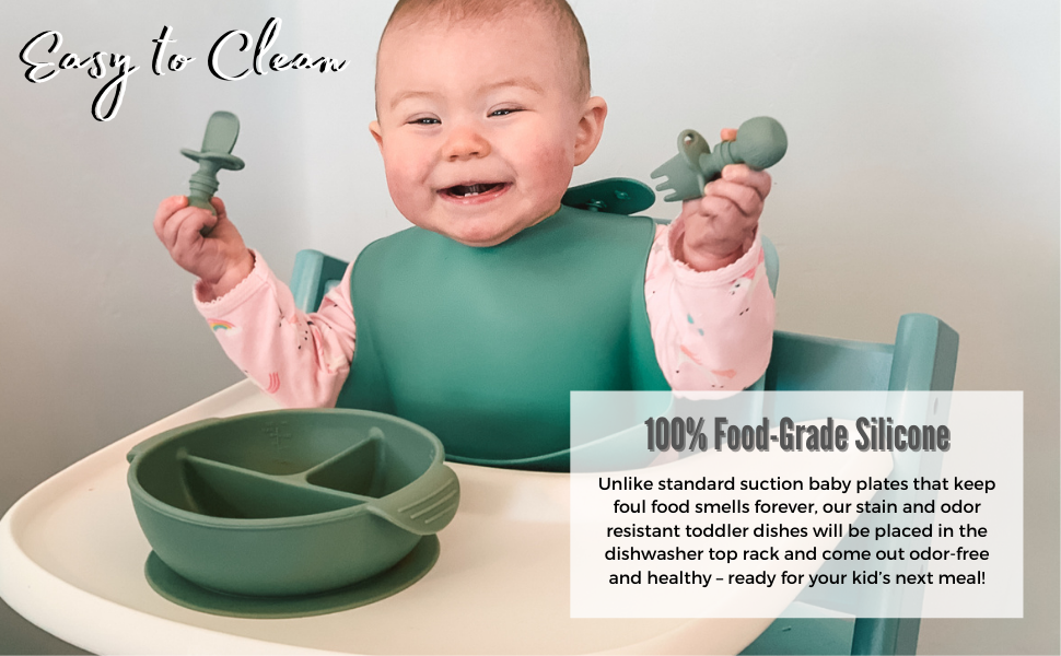 Baby girl on a high-chair smiling while holding BabyBliss silicone spoon and fork.