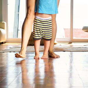Mom & Child walking across a wood floor in their living room.