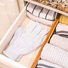 White knit glove in a kitchen drawer.