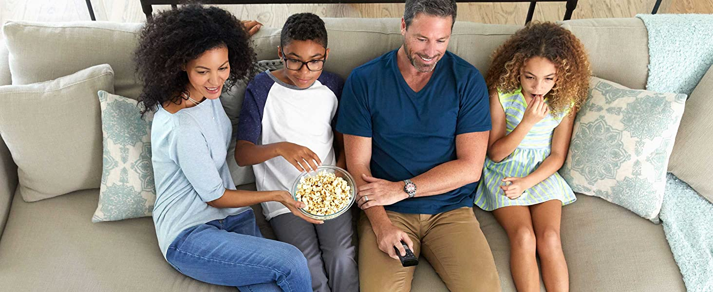 Comfortable family sitting on couch at home together with popcorn