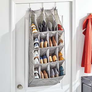 gray shoe organizer filled with shoes hanging on back of white door