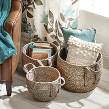 3 natural woven baskets holding throw pillows, books, blanket, teal, brown, cream window curtain