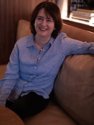author on a couch smiling