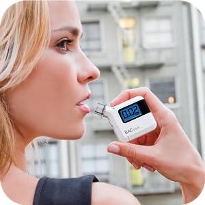 Woman using BACtrack S35 Breathalyzer