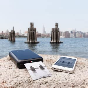 black zip mobile printer printing out picture from smartphone on a beach