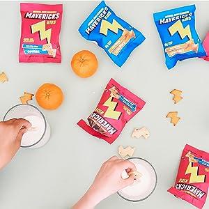 bags of mavericks snacks, hands dipping cookies in milk, oranges