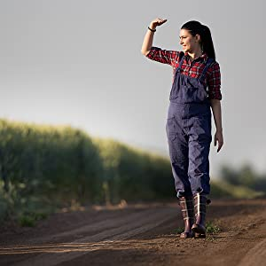 Woman farmer walking down an isle of corn with the sun in her eyes